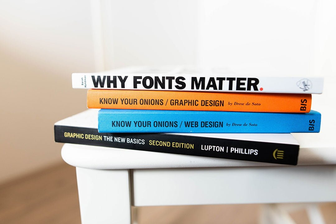 A stack of books about Logo Design, Website Design, Branding, and Graphic Design.