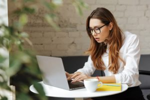 woman using her laptop searching for website designs