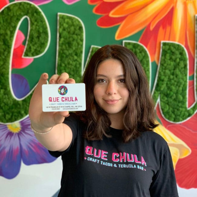 A young girl holding a que chula giftcard