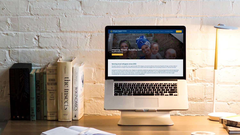 Refugee support center website mockup on laptop on desk
